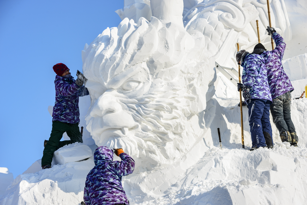 Four artists working on an ice sculpture at the Harbin International Ice and Snow Sculpture Festival