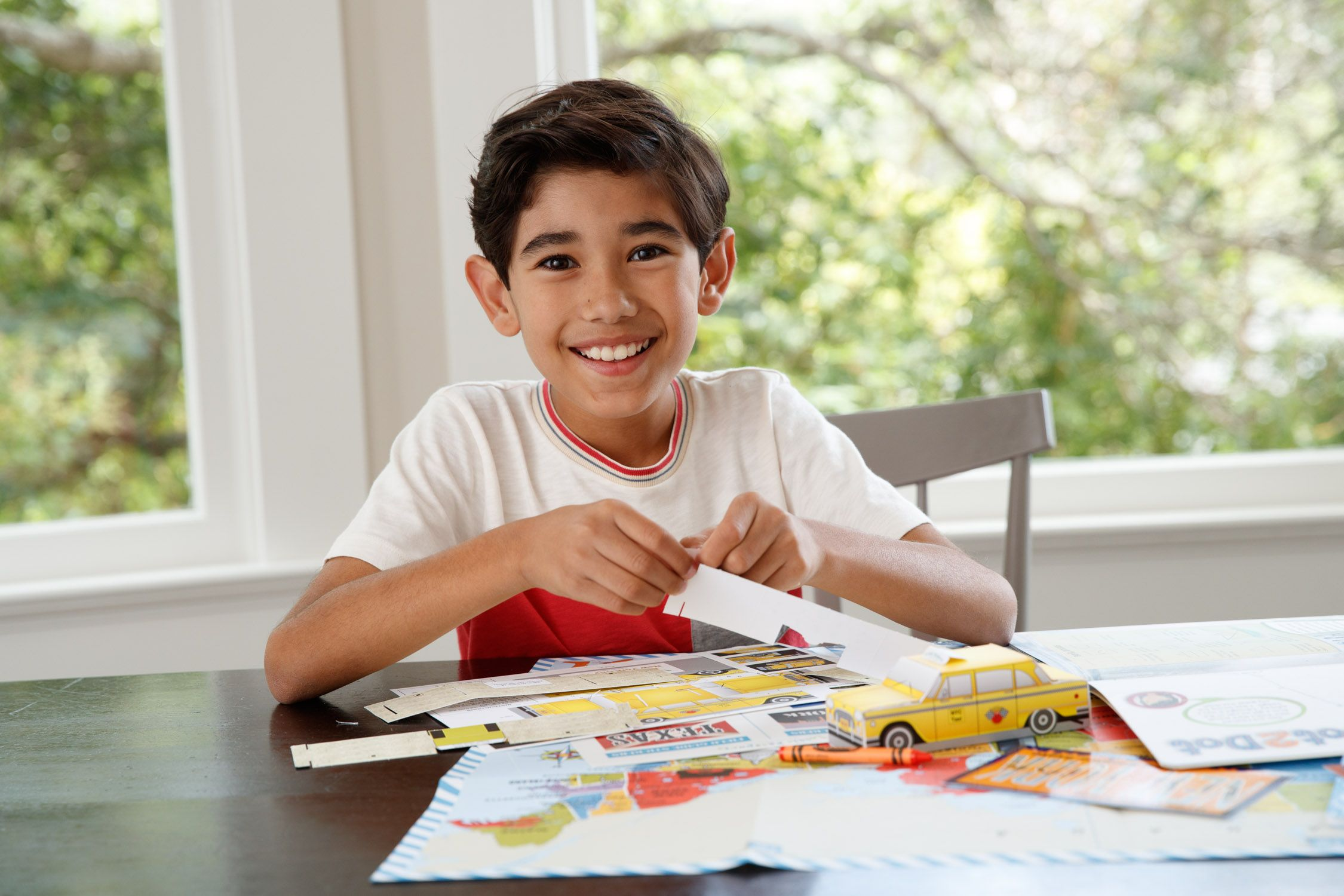 Boy with map on table assembling paper taxi