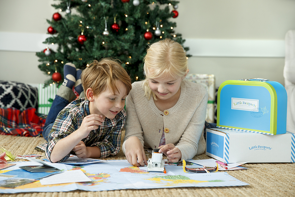Brother and sister with their unique Christmas gift for kids, learning about the world with the educational subscription Little Passports