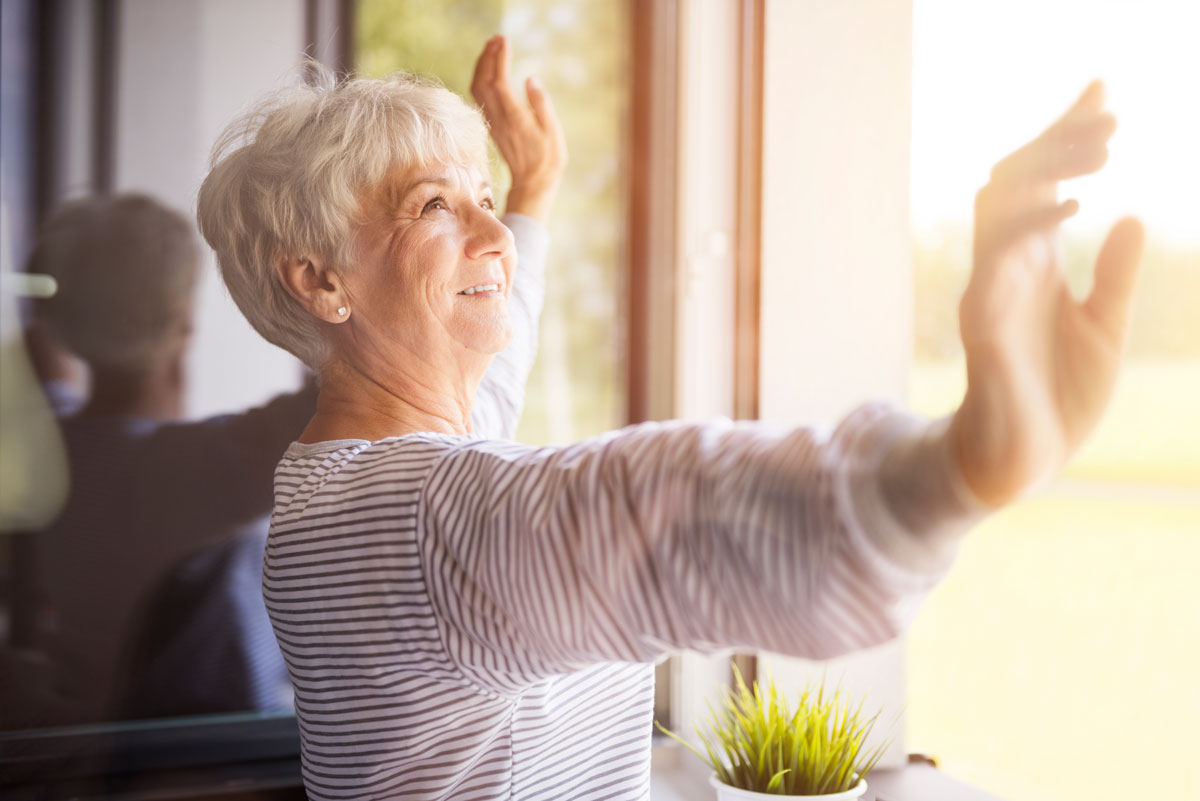 Senior woman stretching and looking out the window