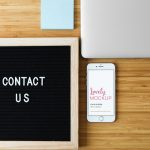 White iPhone Mockup and Contact Us Sign On Desk