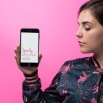iPhone Mockup of a Woman Posing Against a Pink Wall Featured