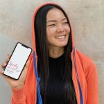 iPhone Mockup and a Smiling Woman with a Hoodie Featured