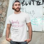 T-Shirt Mockup of a Man Posing in Front of a Graffiti Wall Featured