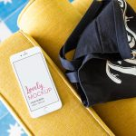 iPhone Mockup Lying on a Yellow Sofa Near a Bag Featured