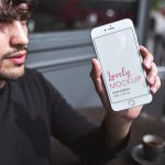 Mockup of a Man with a Beard Showing his iPhone Featured