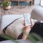 Mockup of a Woman Using an iPhone Sitting on a Sofa Featured