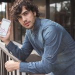 Mockup of a Man with Curly Hair Holding a Gold iPhone Featured