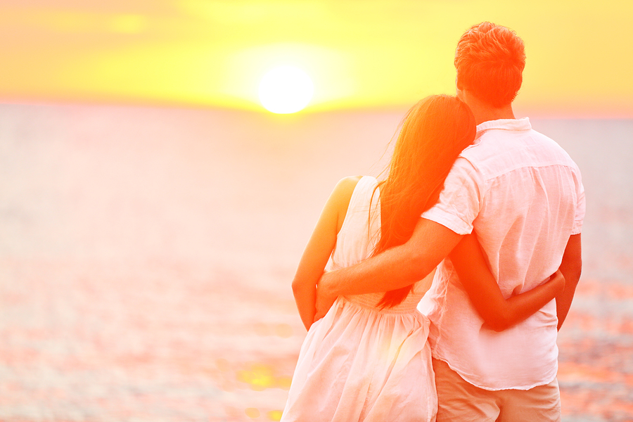 Honeymoon couple romantic in love at beach sunset. Newlywed happy, stress free honeymoon tips, me and you sitting in a honeymoon
