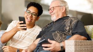 grandson showing grandfather funny meme on phone laughing