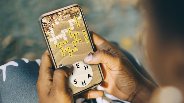 woman plays Wordscapes on her phone
