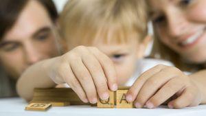 Boy arranging QA Scrabble letter tiles