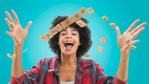 Happy woman throwing up Scrabble tiles