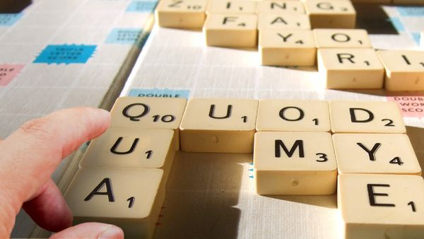 hand pointing at short scrabble words
