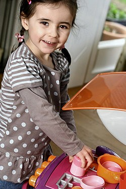 Girl playing with toy oven as examples of observational learning