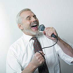 Man singing loudly into a microphone as examples of overconfidence