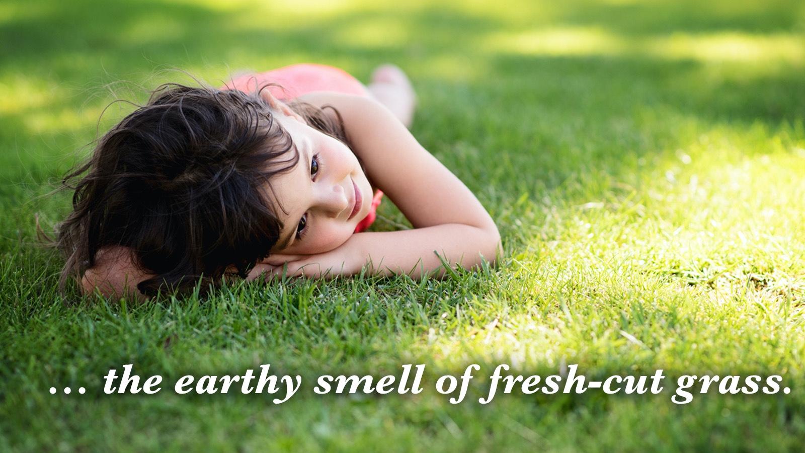 girl smelling fresh-cut grass