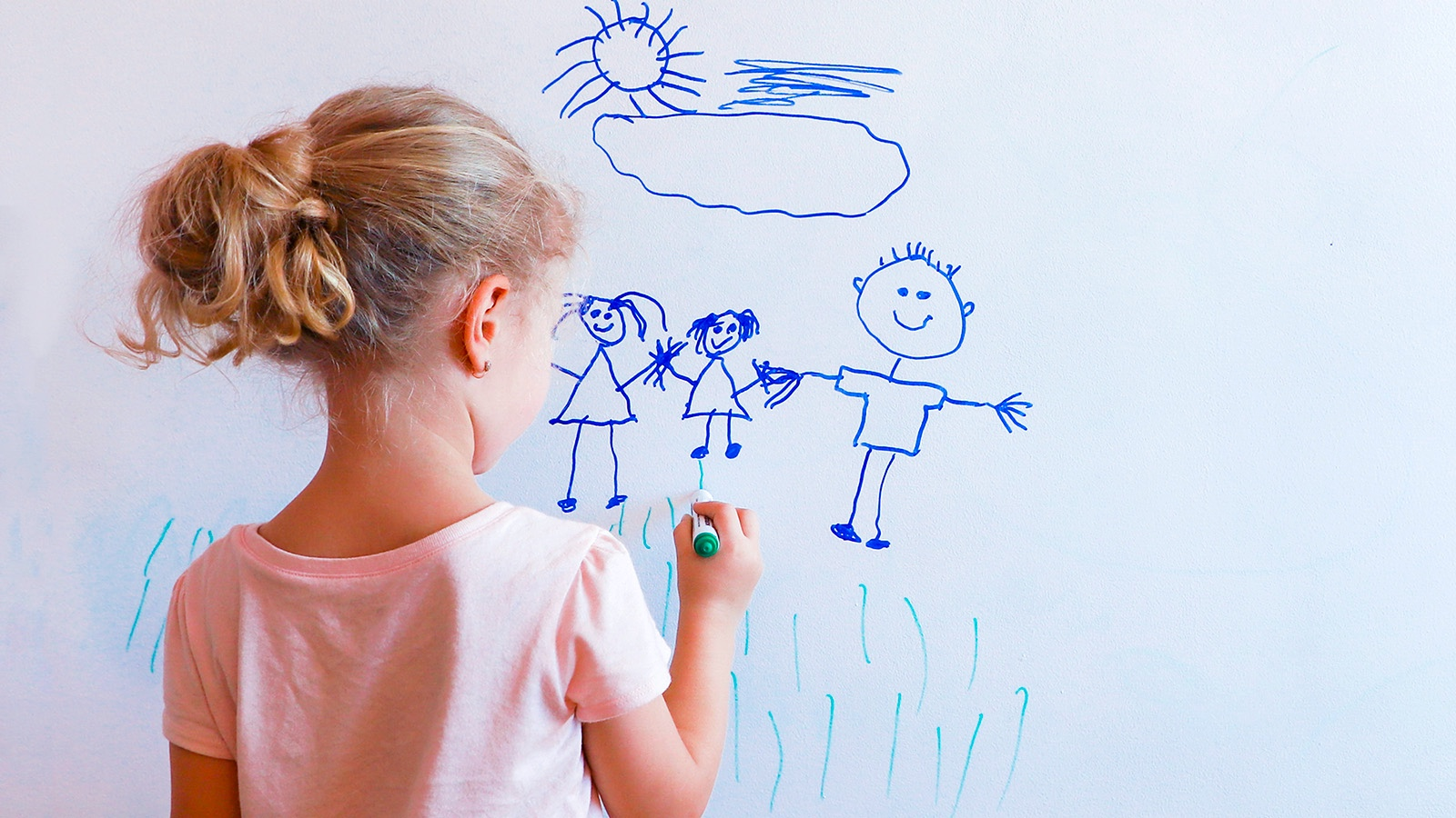 Girl drawing pictionary word on whiteboard