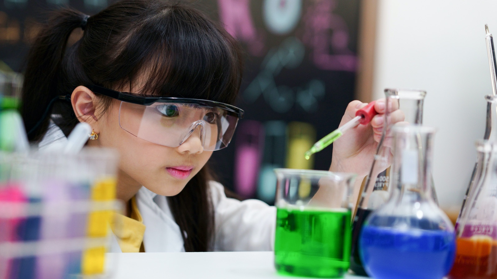 Student performing science experiment with variables