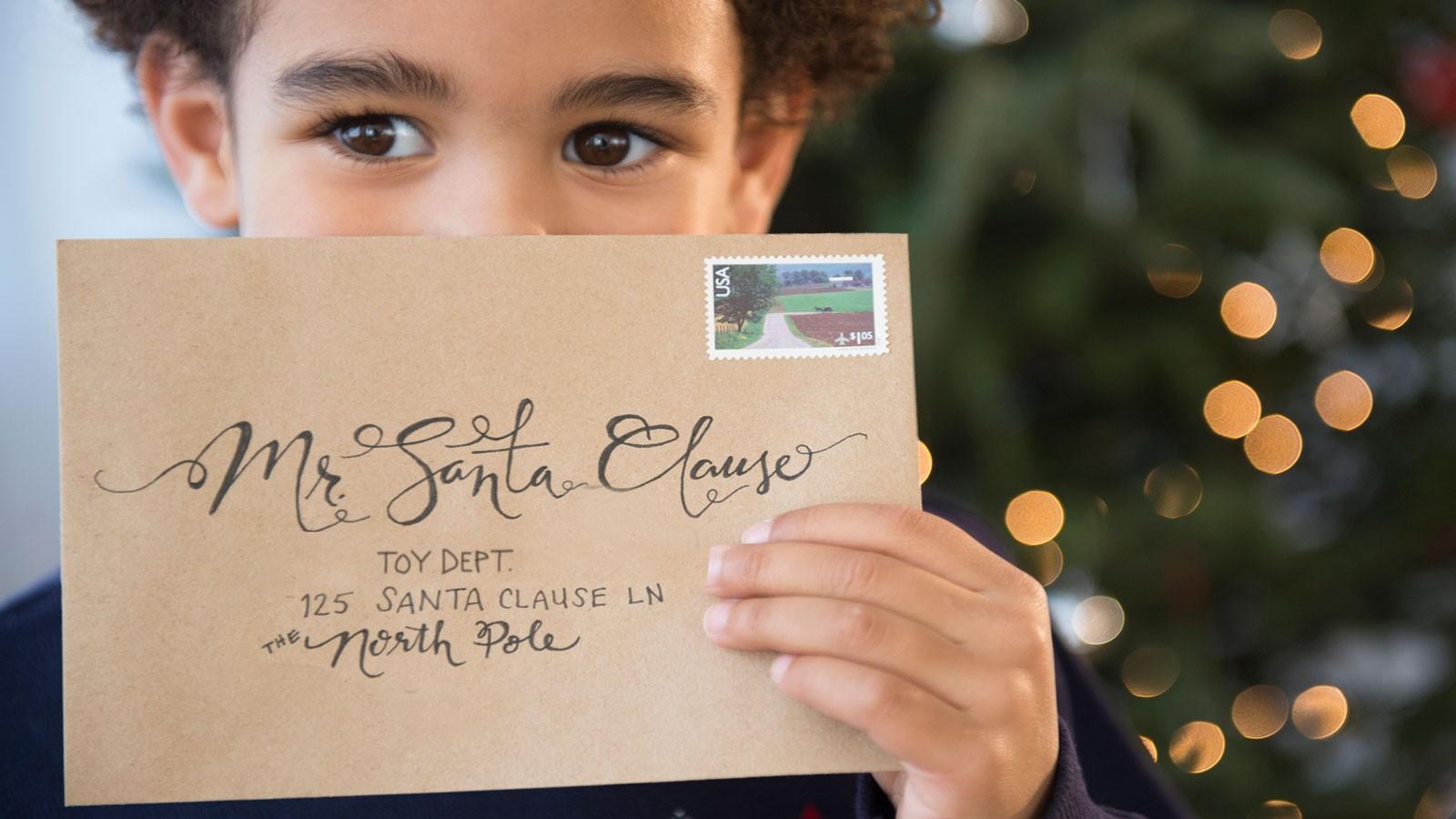 Boy holding letter addressed to Santa