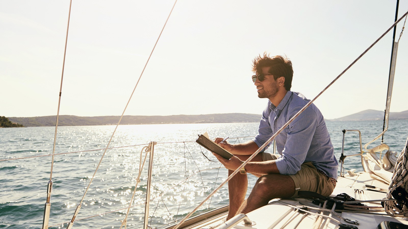 man writing ballad on boat in journal