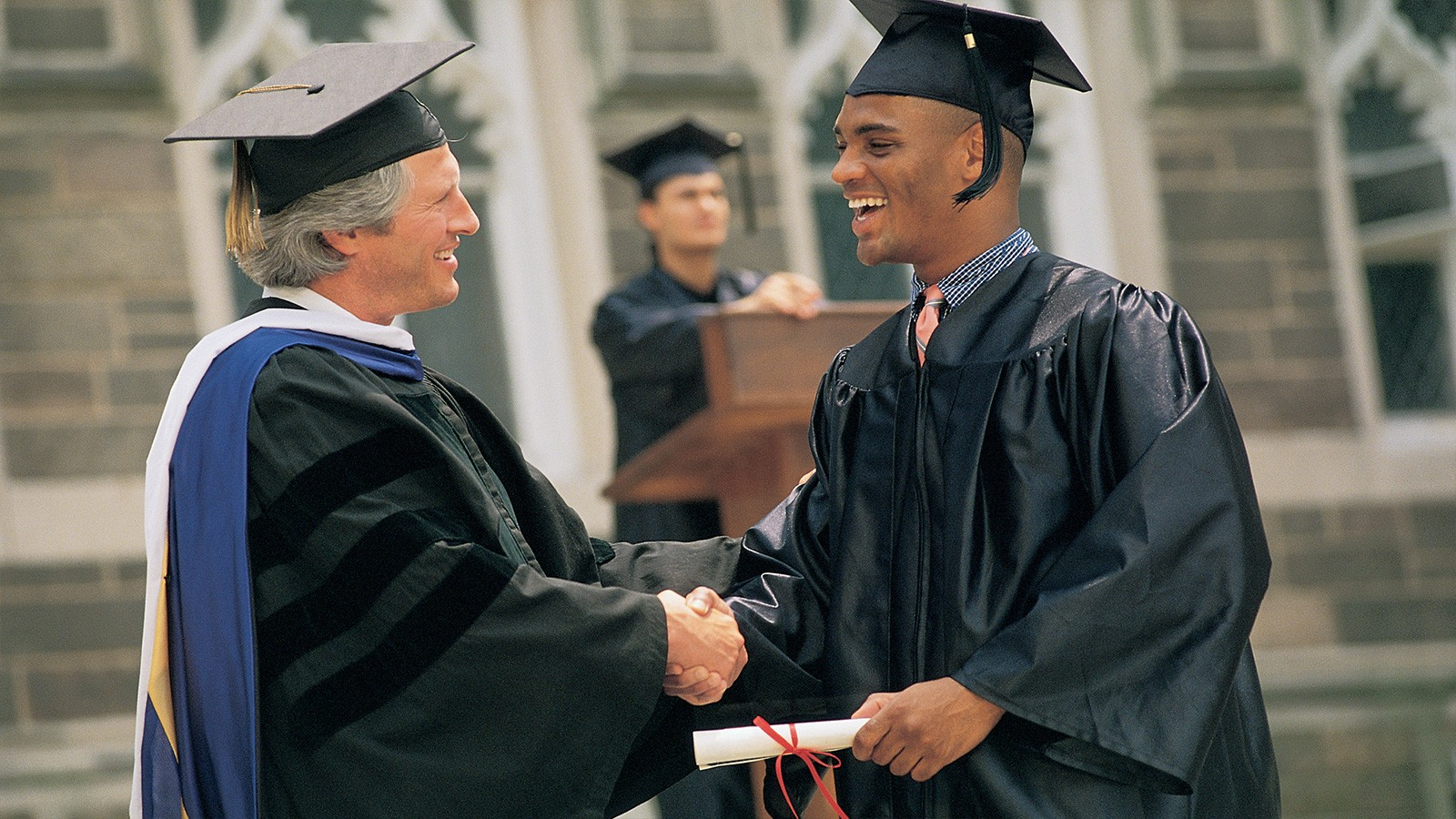 man receiving diploma at graduation