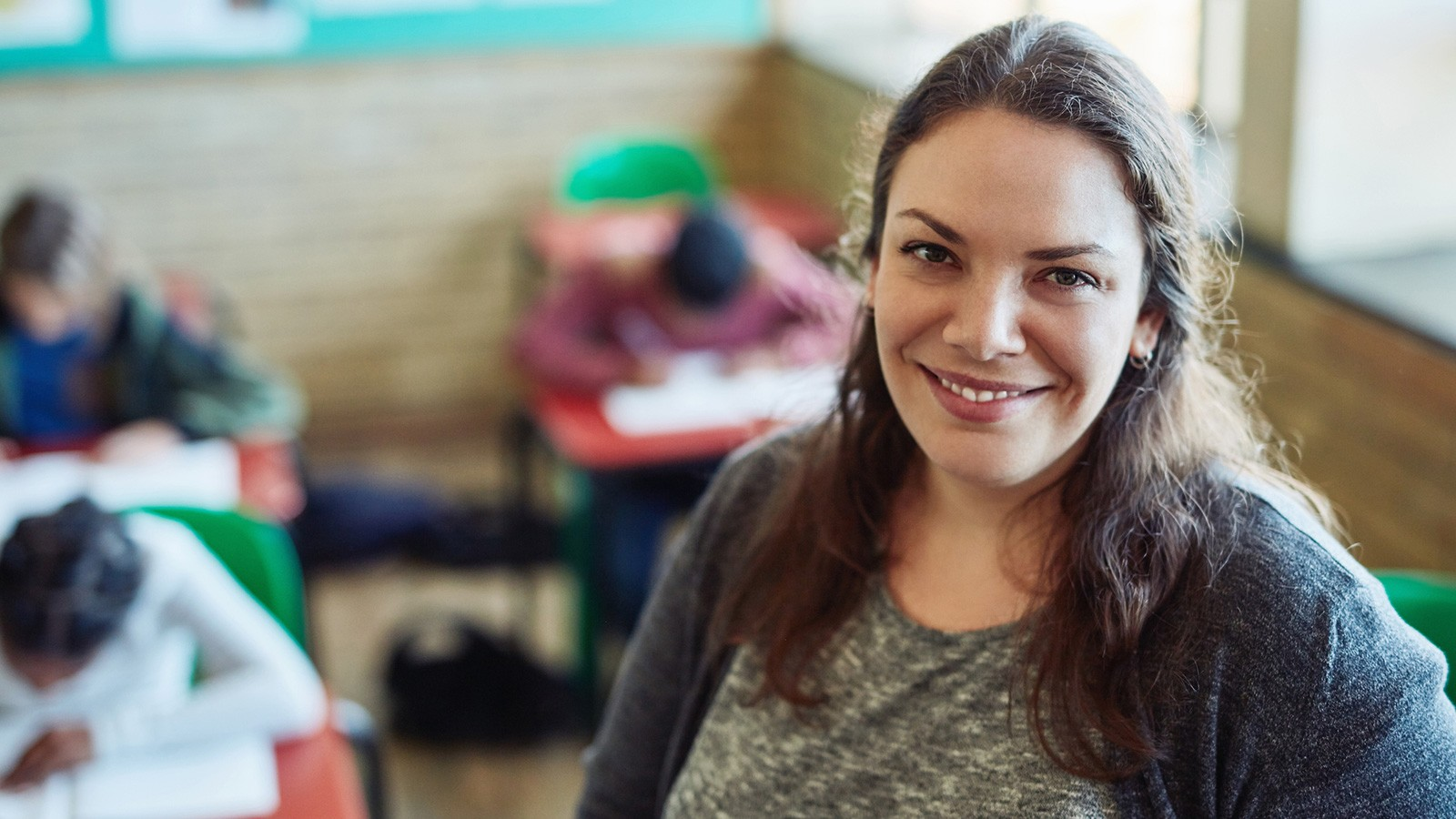 confident smiling woman teacher in classroom