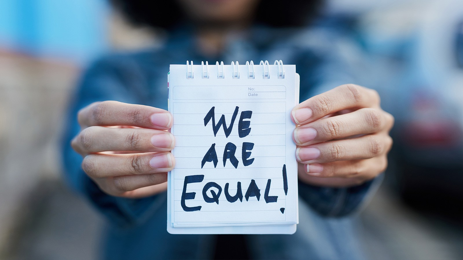 woman holding we are equal sign