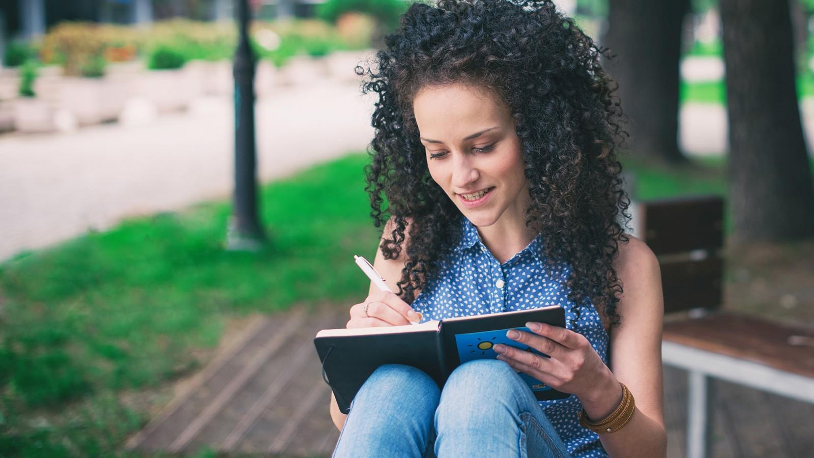 woman writing ballad poem in journal