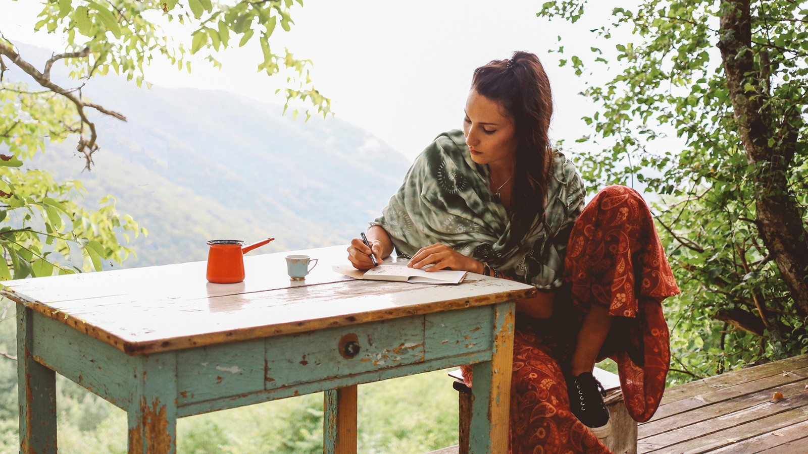 woman writing outdoors at table