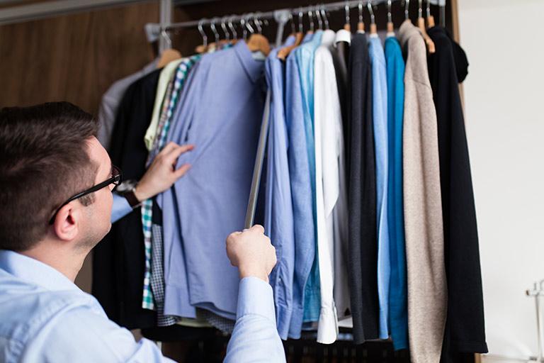 man looking at dress shirts