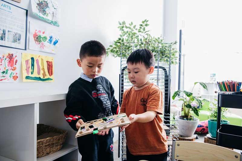 Children engage in conversational skills about their artwork.