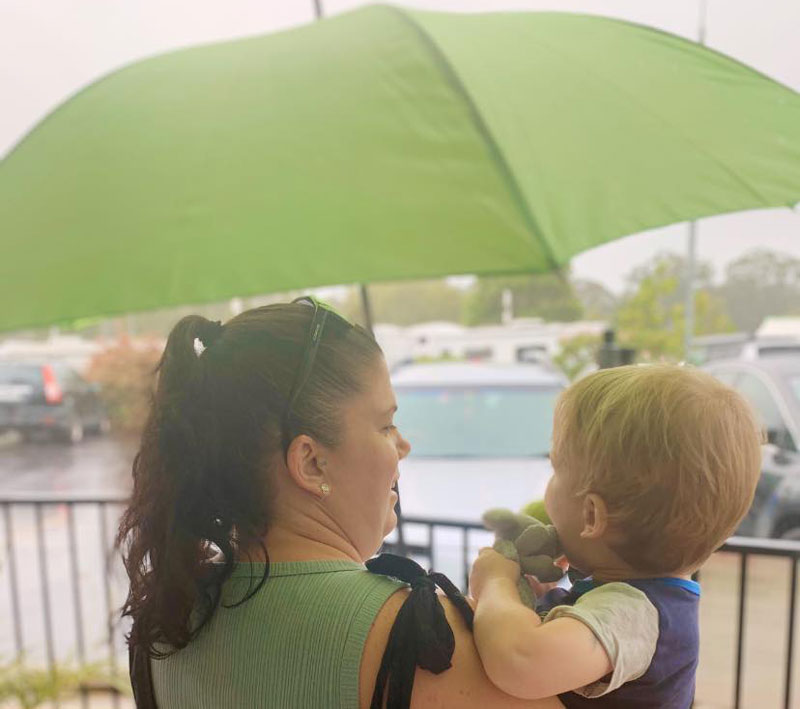 Mum holds an umbrella over babies head. Kindnesses, like umbrellas on wet days, can spark conversations and encourage family engagement.