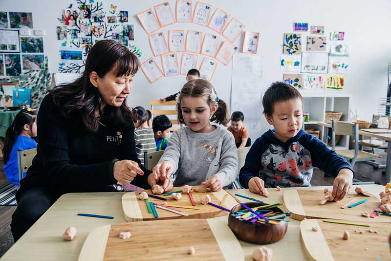 Educator works with children developing their interests and fine motor skills.