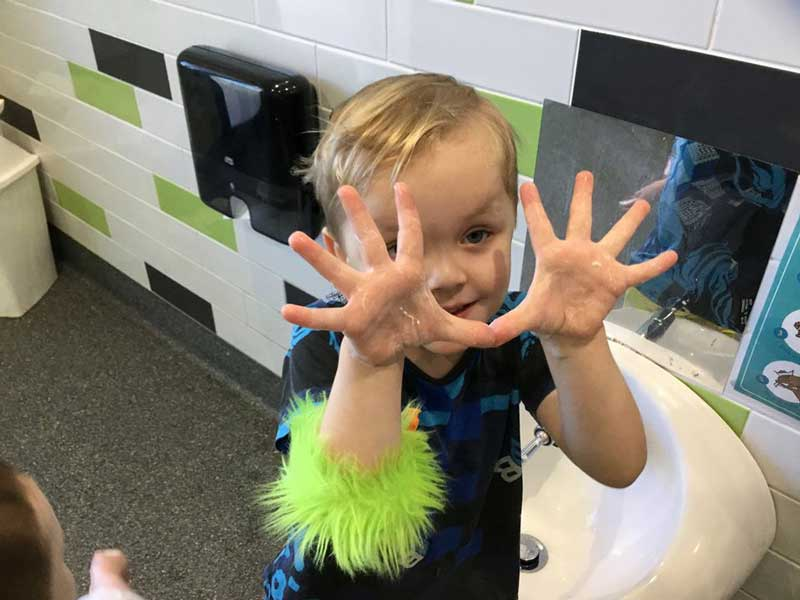 Child shows soap covering his hands as he learns hand washing songs.