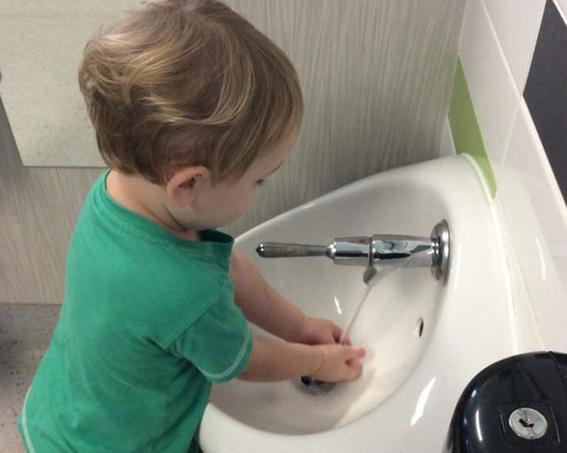 Child washes hand in running water while taking hand washing for kids seriously.
