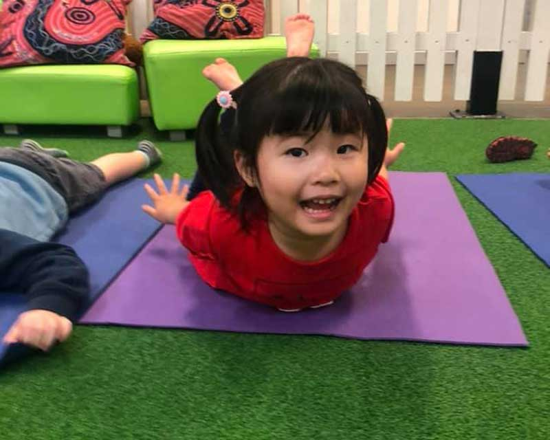Children practice yoga and relaxation meditations at Petit Early Learning Journey.