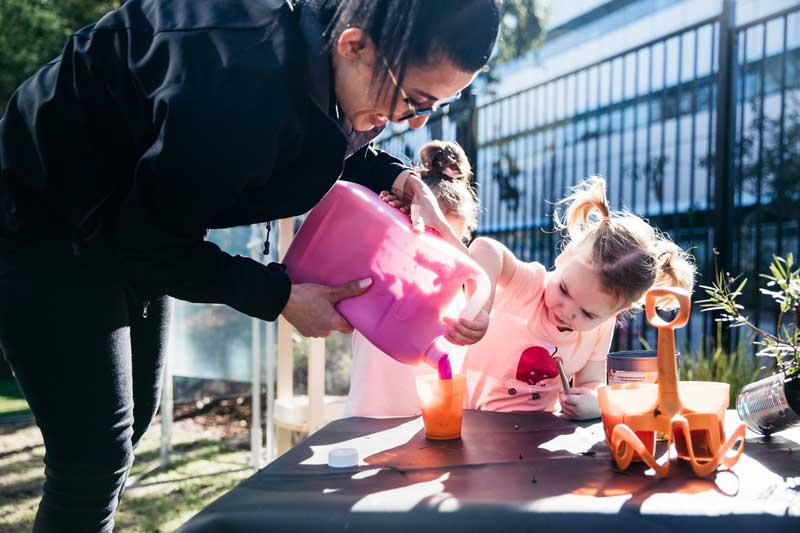 Educator pours paint for children doing sand painting.