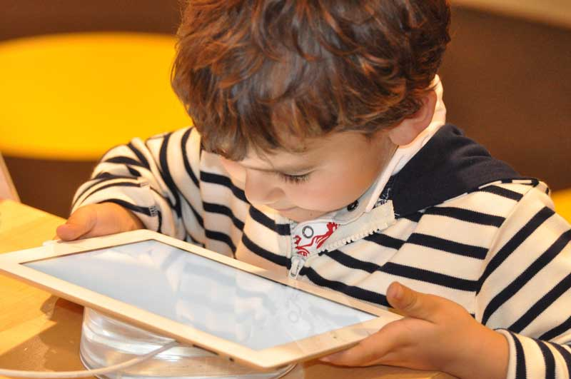 Child learns how to use tablet with the best educational apps for kids