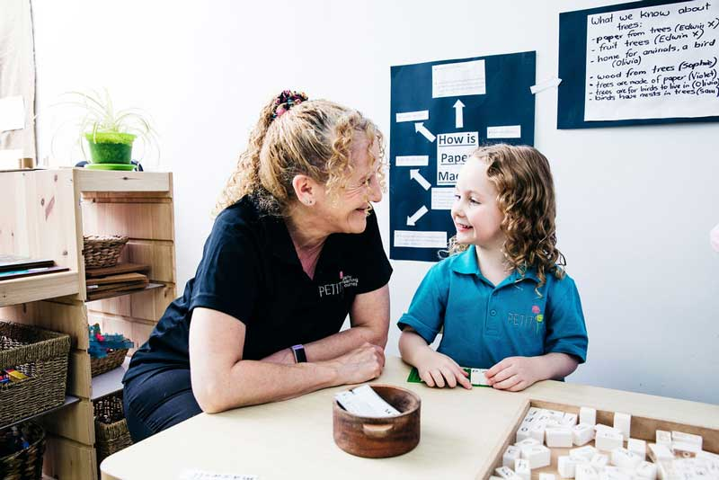 Educator and child engage in a eye contact game for teaching preschoolers conversational skills.