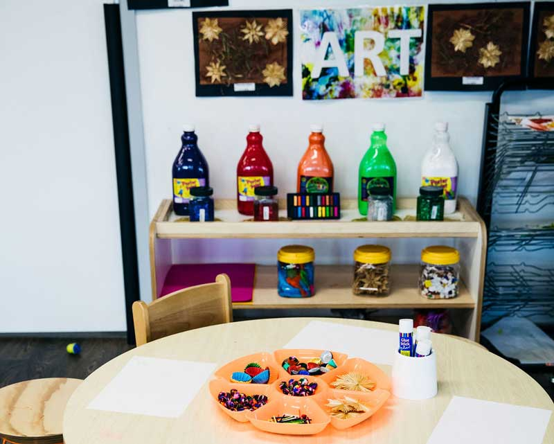 Colourful sand bottles on display in the art corner