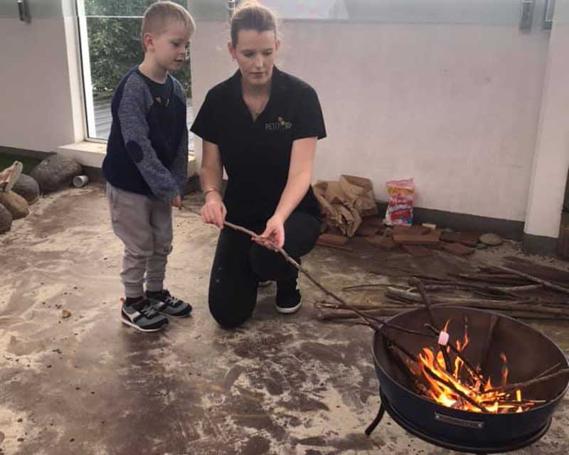 Child and Educator Practises toasting marsh mellows-a fun activity when camping with kids.