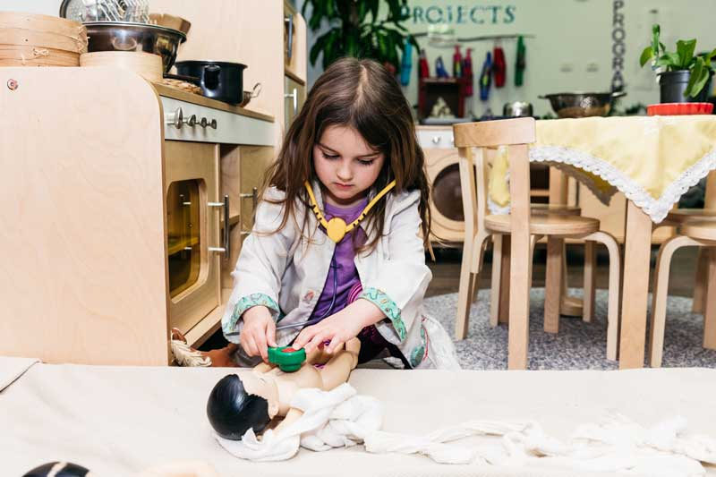 Child roleplays at being a doctor. Roleplaying helps children learn about treating children's burns and other injuries.