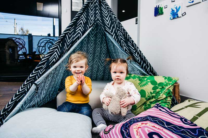 Toddlers await their children's story meditation among pillows and a tepee.