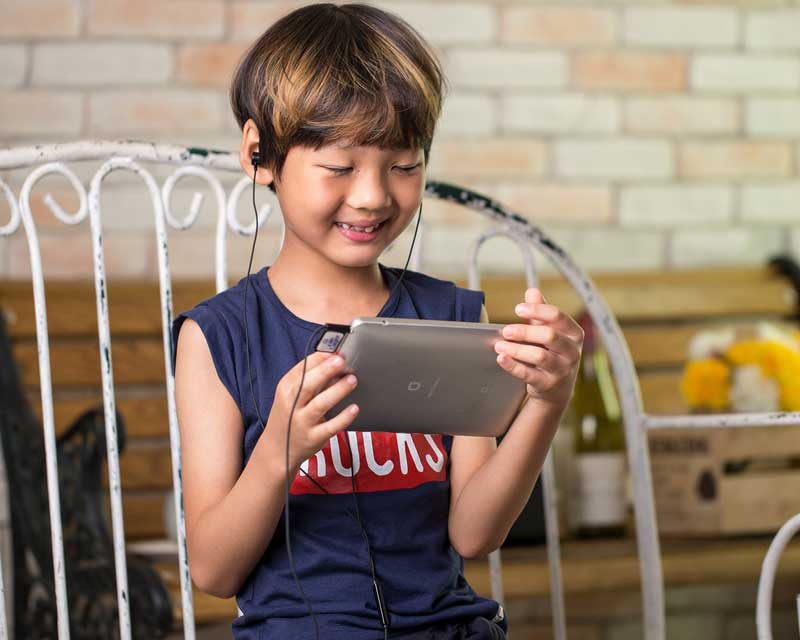 Child uses headphones with ipad and the best apps for 4-year-olds.
