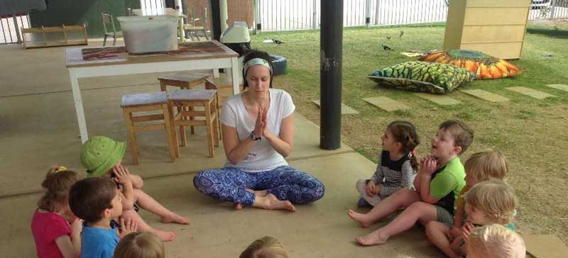 Children sit in a circle as a teacher leads a guided meditation for children.