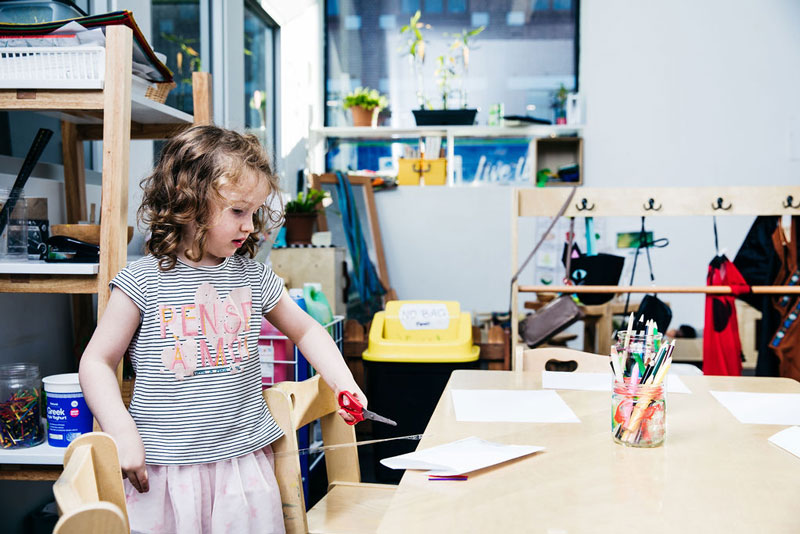 Child uses scissors for Christmas ideas and crafts encouraging the use of fine motor skills.