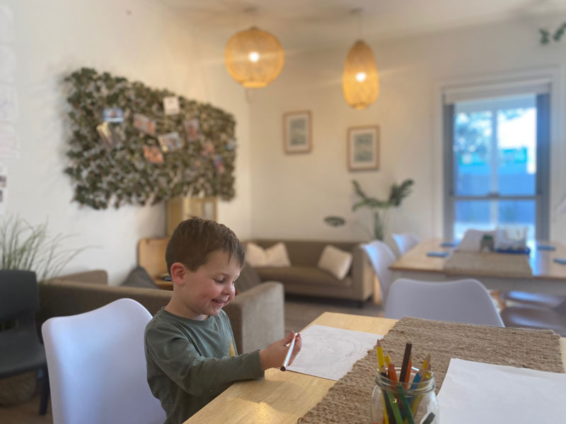 Child sits at desk with art. The soft furnishings engage families in children's learning.