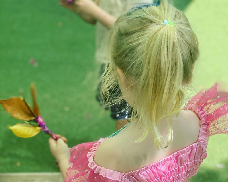 Child holds a nature fairy wand showing her appreciation for the world and its natural resources.