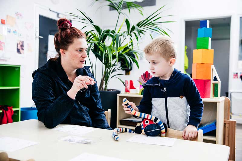 Educator engages child in preschool conversation skills with questions.